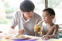 Man talking with little boy and having food together, Family, Leisure Activities
