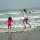 Two girls jumping in water on beach, Wickaninnish Beach Trail, Vancouver Island, Canada