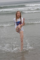 Girl kicking her leg in water, Wickaninnish Beach, Vancouver Island, Canada