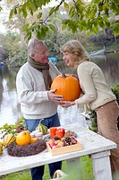 Couple holding large pumpkin