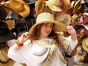 13-year-old girl with long blonde-brown hair and freckles trying on big hat in front of hat display on Venice Boardwalk, Venice, CA