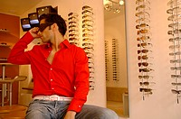 Young man with black hair wearing big sunglasses in a shop full of eyeglasses