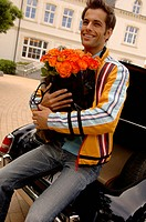 Young man with black hair sitting on a trunk with a bunch of roses in his hands, selective focus