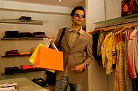 Young man with sunglasses and bags in his hand standing in a clothes shop