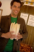 Young man with black hair holding a bunch of asparagus in his hands, selective focus