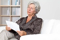 Senior woman reading document on couch