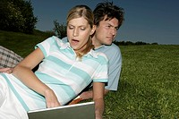 Young couple with laptop in grass