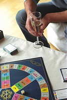 Man holding a Champagne Glass and a Board Game laying on a Table cropped