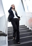 Businesswoman using cell phone on stairs