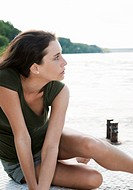 Young woman sitting on jetty at lake