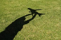 Shadow of boy holding up toy aeroplane