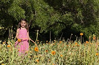 Little girl holding hula hoop standing in field of flowers