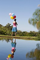 Woman holding balloons standing by lake