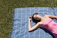 Woman lying on picnic blanket with eyes closed