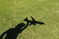 Shadow of child playing with toy aeroplane