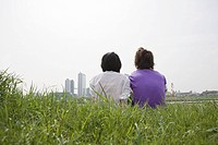 Young couple on grass looking towards city