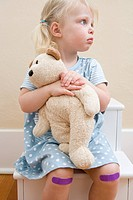 Girl with teddy bear and plasters on knees (thumbnail)