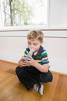 Boy using asthma inhaler with spacer (thumbnail)