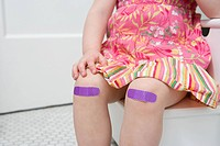 Girl with plasters on her knees