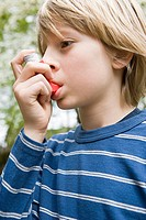 Boy taking asthma inhaler