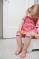 Crying girl with plasters on knees