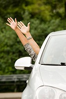 Two people with their hands out of the car window