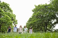 Five young friends walking in the park