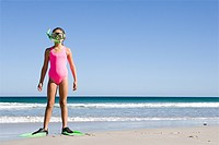 Young girl standing on beach in flippers and snorkel mask
