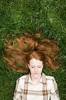 Ginger haired woman sleeping on grass