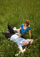 man, woman lying in grass with flowers