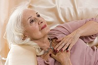 Glamorous senior woman lying on satin