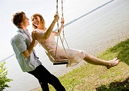 woman and man kissing on swing