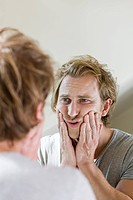 Man looking in mirror and touching face