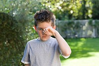 Boy rubbing eye
