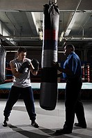 Boxer and coach with heavy bag