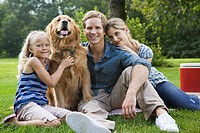 Family in the park with golden retriever (thumbnail)