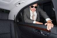 Businessman looking in the back of a car