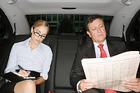 Two businesspeople in the back of a car