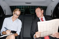 Businesspeople in the back of a car
