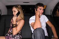 Couple using cellular telephones in car