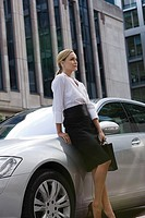 Businesswoman leaning on a car