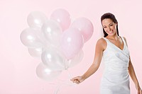 Bride holding a bunch of balloons