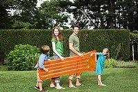 Family carrying an inflatable mattress