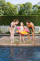 Parents with daughter by the pool