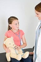 Doctor and girl with teddy bear
