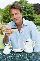 Man having tea outdoors