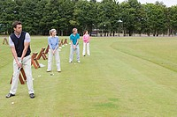 Four golfers on a driving range (thumbnail)