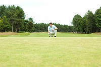 Male golfer crouching on the fairway