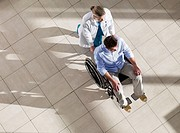 Doctor pushing man in wheelchair
