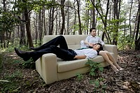 business man and woman on sofa in forest glade